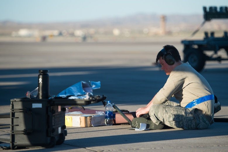 U.S. Air Force Airman 1st Class Zachary Perry, 94th Aircraft Maintenance Unit integrated avionics journeyman, runs checks after performing maintenance on an F-22 Raptor at Nellis Air Force Base, Nevada, July 16, 2019.