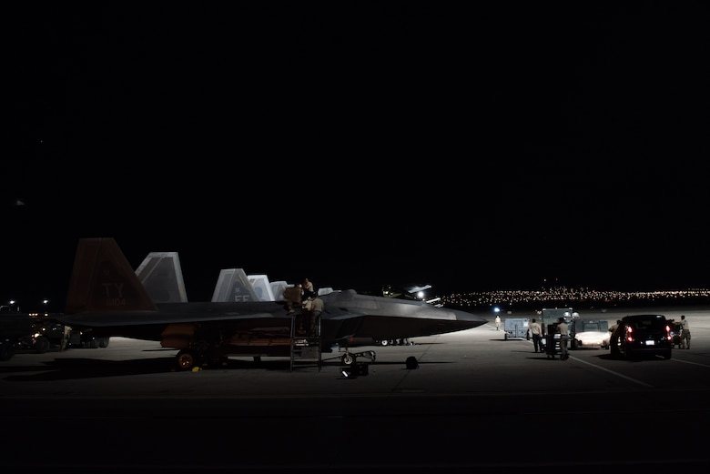 U.S. Air Force integrated avionics specialists from the 94th Aircraft Maintenance Unit perform maintenance on an F-22 Raptor at Nellis Air Force Base, Nevada, July 22, 2019.