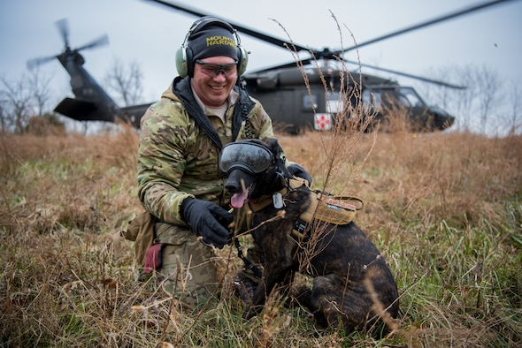 Tech. Sgt. Rudy Parsons, a pararescueman with the Kentucky Air National Guard's 123rd Special Tactics Squadron, and his search and rescue dog, Callie, exit a UH-60 Black Hawk helicopter as part of Callie's familiarization training at the Boone National Guard Center in Frankfort, Ky., Nov. 29, 2018. Callie is currently the only search and rescue dog in the Department of Defense. (U.S. Air National Guard photo by Staff Sgt. Joshua Horton)
