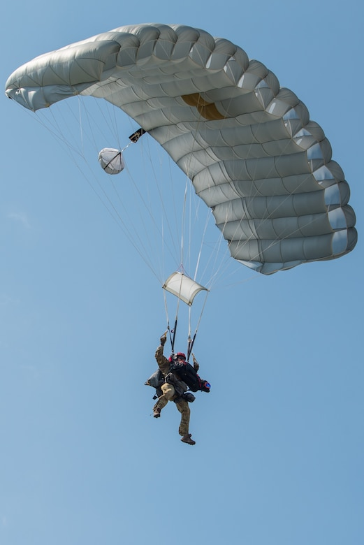 Master Sgt. Rudy Parsons, a pararescueman with the Kentucky Air National Guard's 123rd Special Tactics Squadron, and Callie, his search and rescue dog, complete a parachute insertion into Volk, Wis., July 16, 2019, as part of Patriot North, an annual domestic operations exercise designed to provide natural disaster-response training. Callie is currently the only search and rescue dog in the Department of Defense. (U.S. Air National Guard photo by Staff Sgt. Joshua Horton)