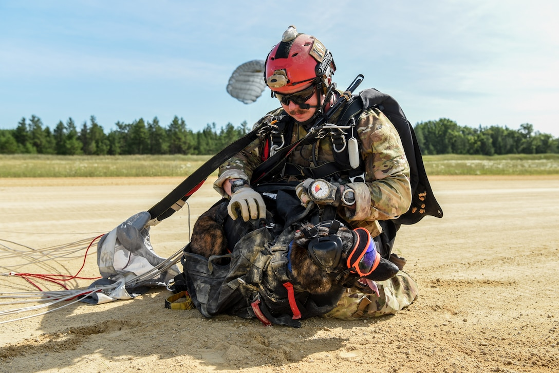 Master Sgt. Rudy Parsons, a pararescueman with the Kentucky Air National Guard's 123rd Special Tactics Squadron, and Callie, his search and rescue dog, land at Volk Field, Wis., July 17, 2019, as part of a domestic operations exercise. Callie is currently the only search and rescue dog in the Department of Defense. (U.S. Air National Guard photo by Staff Sgt. Joshua Horton)