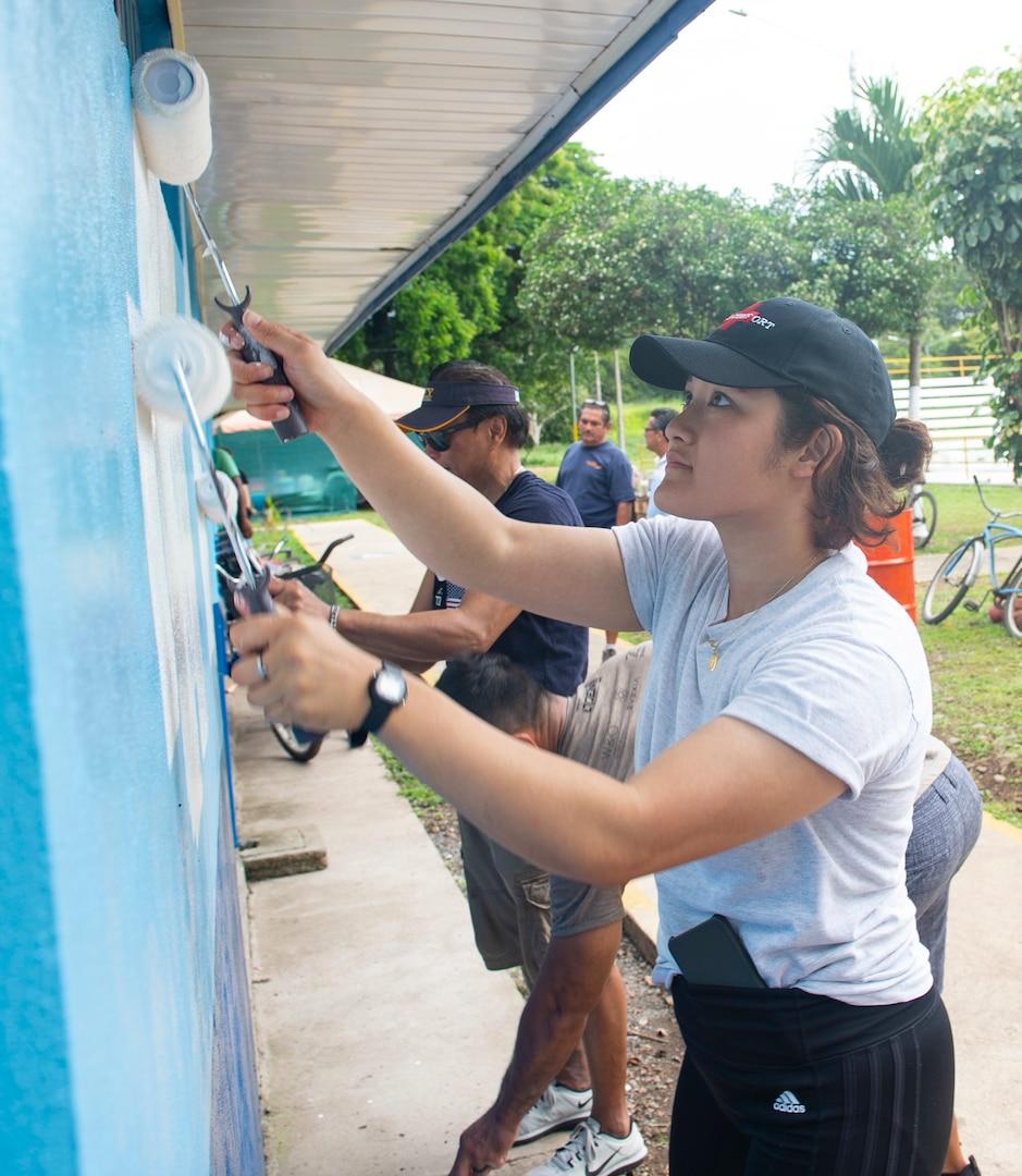 A Sailor helps paint a community pool.