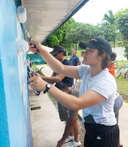 A Sailor helps paint a community pool.