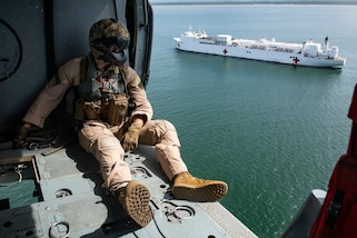 A Sailor looks out from a helicopter.