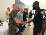 Military personnel shake hands.