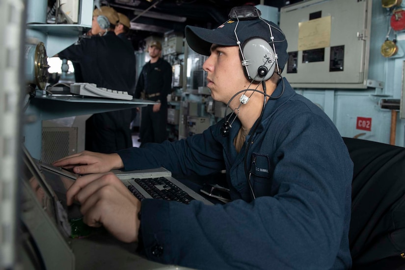 Sailor seated at a console stands watch.