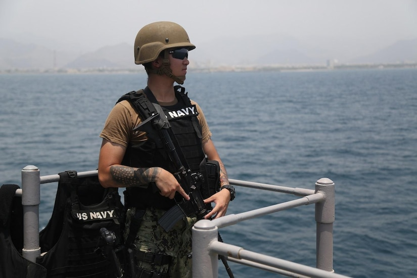 Sailor wearing a black vest and a green helmet stands watch on a ship.