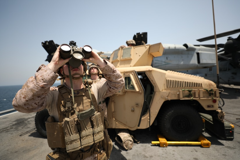 Marine looks skyward through binoculars.