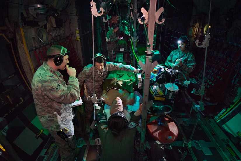 Flight nurse and aeromedical technician course students care for simulated patient during aeromedical evacuation mission aboard C-130 mockup at