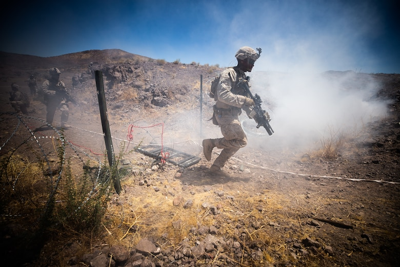 U.S. Marine Corps Pfc. Trevor M. Banks, fireteam leader, Company I, 3rd Battalion, 7th Marine Regiment, 1st Marine Division, moves through a breach to attack an objective during a squad attack at Marine Corps Air Ground Combat Center, Twentynine Palms, Calif., July 15, 2019. The training was conducted to validate the squad leaders capabilities to lead and control their squads while integrating supporting arms in a deliberate attack.
