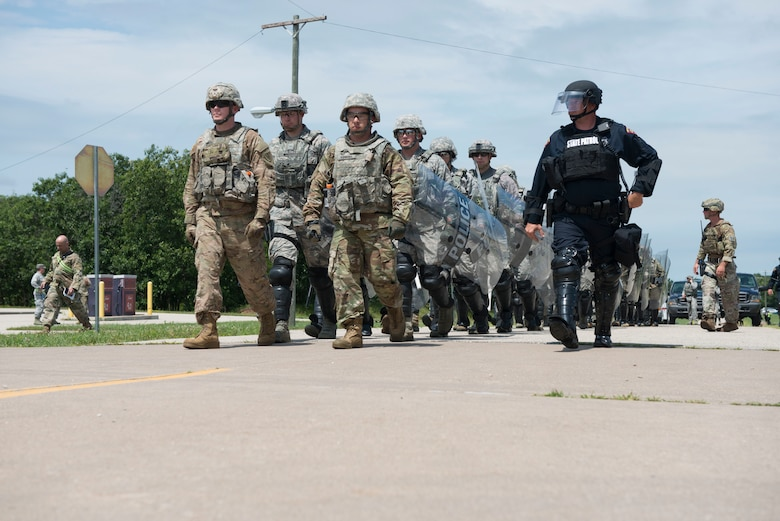 National Guardsmen assigned to the New Hampshire Army National Guard and the New Hampshire and Connecticut  Air National Guard march in formation with members of the Wisconsin State Patrol in a riot-control scenario during the PATRIOT North 19 domestic operations exercise, July 18, 2019 at Fort McCoy, WI. PATRIOT North is an annual domestic operations exercise, which tests the ability of the National Guard to work together with local, state and federal entities to respond to emergencies. (U.S. Air National Guard photo by Tech. Sgt. Tamara R. Dabney