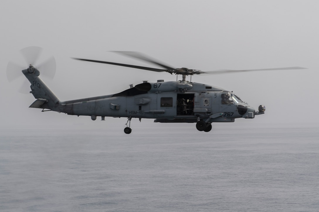A military helicopter flies over a grey ocean.
