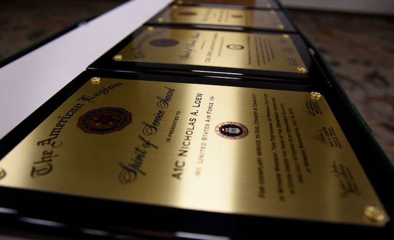 Spirit of Service Award plaques are displayed on a table during the annual American Legion Department Convention in Spokane, Washington, July 19, 2019. The Legion gives the Spirit of Service Awards annually to members from each branch who excel in their performance on-duty and are also actively involved in their local community. (U.S. Air Force photo by Senior Airman Jesenia Landaverde)