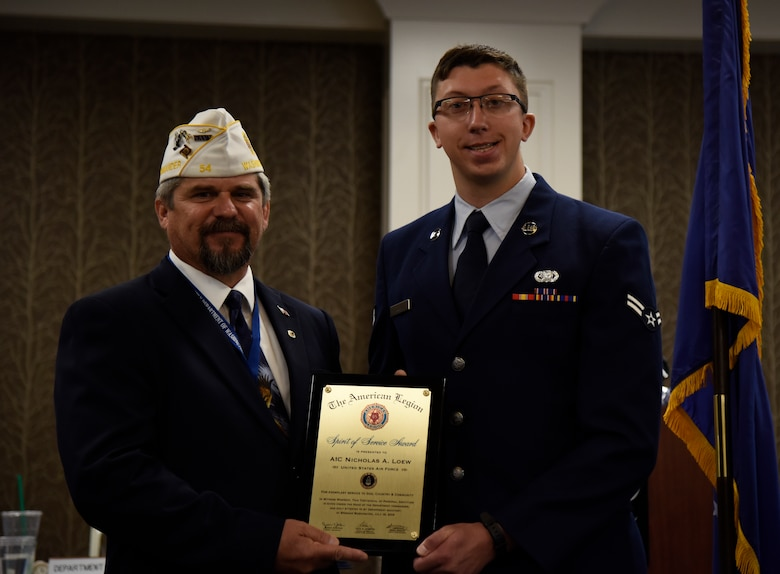 Gary Roach, The American Legion department commander, presents the Spirit of Service Award to Airman 1st Class Nicholas Loew, 92nd Logistics Readiness Squadron fuels distribution operator, during the annual American Legion Department Convention in Spokane, Washington, July 19, 2019. A commitment to the local community led to Loew selflessly volunteering in 33 separate events, for a total of 364 hours. Furthermore, he rallied nineteen volunteers to serve over 3 thousand dinners to less fortunate at the City Gate homeless shelter. (U.S. Air Force photo by Senior Airman Jesenia Landaverde)