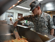 Senior Airman Joseph Santos, 99th Force Support Squadron food service journeyman, prepares lunch for service members during Red Flag 19-3 at Nellis Air Force Base, Nev., July 18, 2019. Red Flag is a combat training exercise involving the U.S. Air Force and its joint and coalition partners. (U.S. Air Force photo by Tech. Sgt. Bryan Magee)