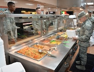 Airman 1st Class Riley, 319th Force Support Squadron food service journeyman, Grand Forks AFB, N.D., serves lunch for service members during Red Flag 19-3 at Nellis Air Force Base, Nev., July 18, 2019. Red Flag was established in 1975 to better prepare our forces for combat. Lessons from Vietnam showed that if a pilot survived 10 combat missions, his chances of surviving remaining missions increased significantly. (U.S. Air Force photo by Tech. Sgt. Bryan Magee)
