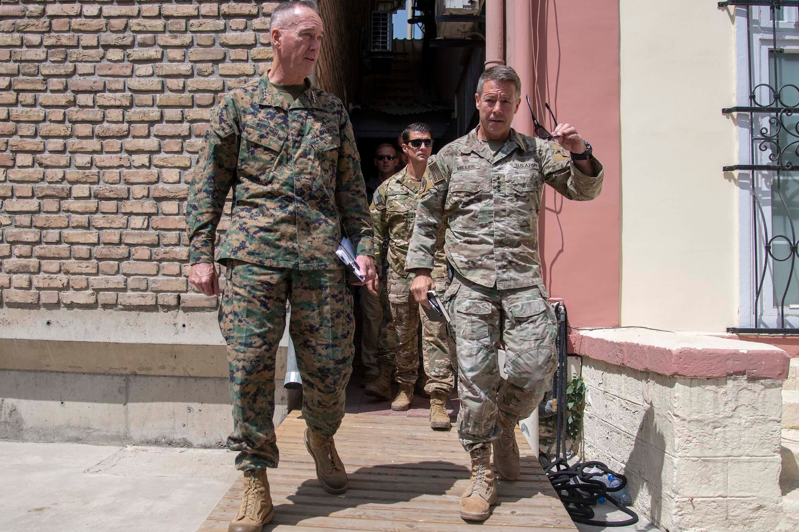 Two generals in camouflage uniforms talk while walking.