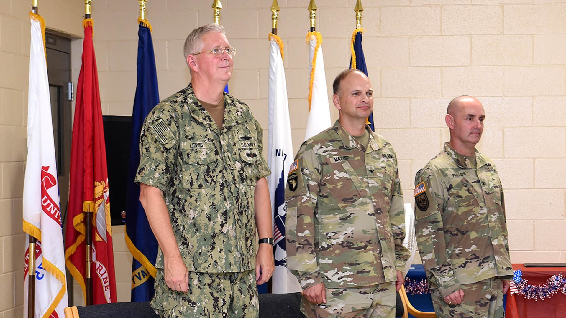 Three commanders standing at attention in front of U.S. and service flags.