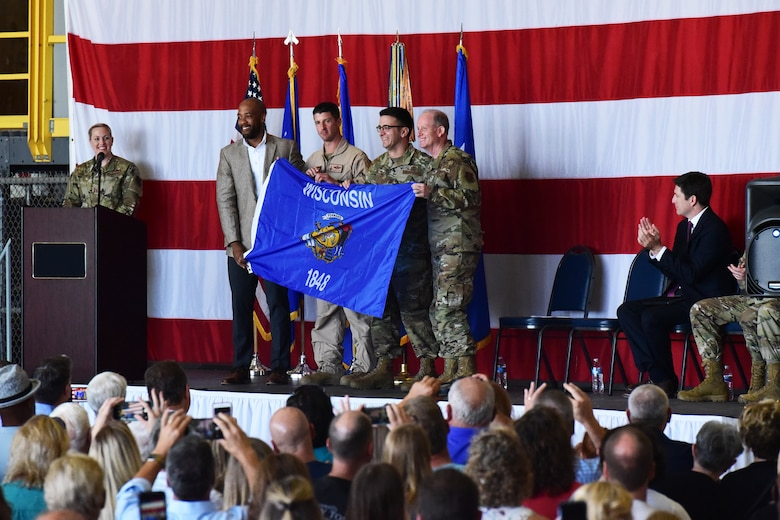 Wisconsin Lt. Gov. Mandela Barnes and U.S. Air Force Maj. Gen. Donald Dunbar, the adjutant general of Wisconsin, present the Wisconsin flag to Lt. Col. Tim Dyer and Maj. Scott Paeth, both deploying Airmen of the 115th Fighter Wing, at a send off ceremony held at Truax Field, Madison, Wis. on July 21, 2019.  The 115th Fighter Wing deployed approximately 300 personnel and a number of aircraft to Afghanistan in support of Operation Freedom Sentinel and NATO's Resolute Support. (U.S. Air National Guard photo by Staff Sgt. Kyle Russell)