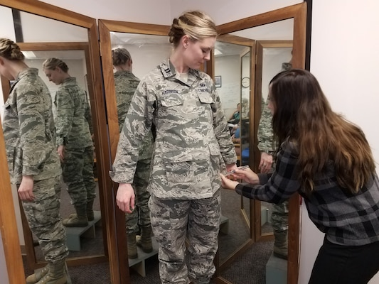 Stacey Butler (right) a clothing designer with the Air Force Life Cycle Management Center's Air Force Uniform Office, measures Capt. Taylor Harrison's maternity Airman Battle Uniform. The new uniforms were designed and developed by the office and are available to pregnant Airmen around the world.