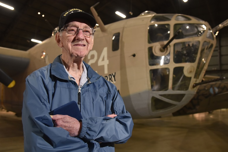 """World War II veteran 1st Lt. Joseph Kollenberg poses in front of the B-24 """"Strawberry Bitch"""" at the National Museum of the United States Air Force, July 24. Kollenberg served as a B-24 Navigator in the U.S. Army Air Corps from 1944-1945, completing more than 27 combat missions over Northern France, Germany, the Ardennes and Central Europe.  (Air Force photo/Ken LaRock)"""