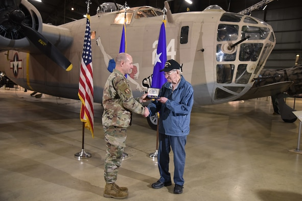 Maj. Gen. Carl Schaefer, Air Force Materiel Command deputy commander, presents service medals to 93-year-old World War II veteran 1st Lt. Joseph Kollenberg at the National Museum of the United States Air Force, July 24. Schaefer presented Kollenberg with the  Distinguished Flying Cross, the Air Medal with three Oak Leaf Clusters, and the European, African, and Middle Eastern campaign service medals to replace those misplaced in the 70 years since the veteran left active duty service. (Air Force photo/Ken LaRock)