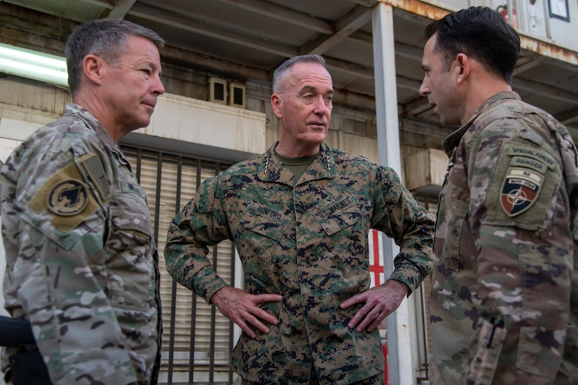 Three service members in camouflage uniforms have a conversation.