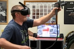 Travis McGreger, Shop 71, Painters, Blasters and Tilesetters, training instructor, demonstrates how the virtual reality paint sprayer trainer works July 10 in a Continuous Training and Development classroom in Building 460.