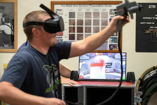 Travis McGreger, Shop 71, Painters, Blasters and Tilesetters, training instructor, demonstrates how the virtual reality paint sprayer trainer works July 10, 2019, in a Continuous Training and Development classroom in Building 460.