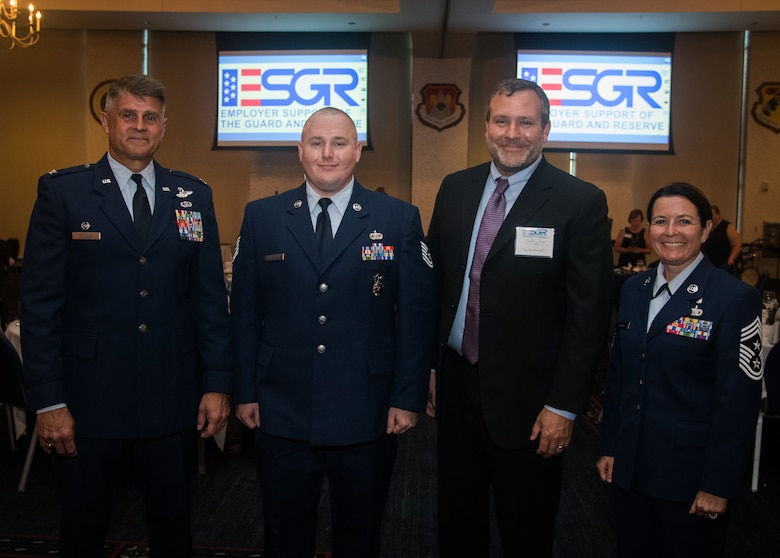 Col. Glenn Collins, commander, 932nd Airlift Wing, left, Tech. Sgt. Christopher Wallace, 932nd Security Forces, Mr. Jeffery Rush, Icon Mechanical and 932nd Command Chief Master Sgt. Barbara Gilmore all pose for a portrait during the Employer Support of the Guard and Reserve award banquet, July 19, 2019, Scott Event Center, Scott Air Force Base, Illinois. (U.S. Air Force photo by Christopher Parr)