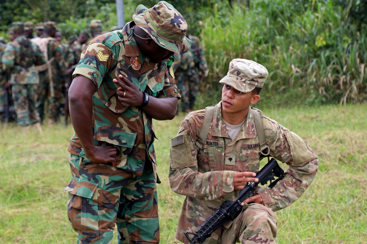 A soldier from Ghana and a U.S. soldier, both in camouflage uniforms, talk while training together.