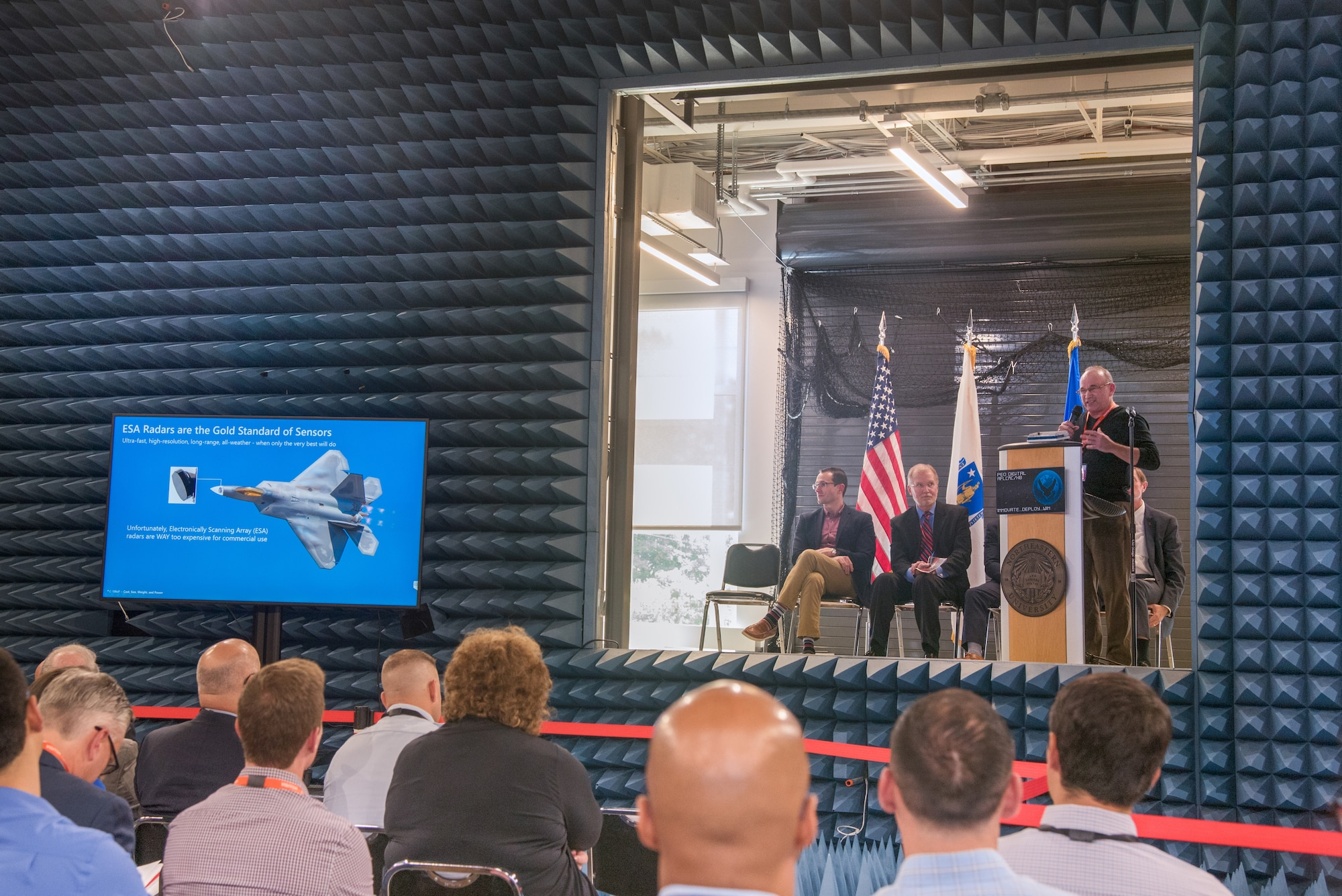 From Right: Jeff Finan, vice president of business development for Washington-based Echodyne Corp., presents radar technology information after earning an on-the-spot contract for development with the U.S. Air Force during Unmanned Aerial Systems Pitch Day, July 24, at Northeastern University's Innovation Campus as Steven Wert, program executive officer Digital, and Dr. William Roper, Air Force assistant secretary for Acquisition, Technology and Logistics, look on from the stage. (U.S. Air Force photo by Todd Maki)
