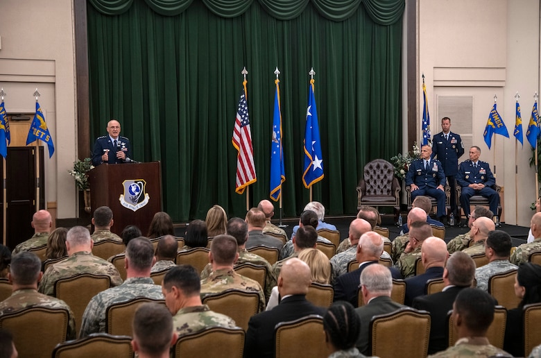 Gen. Arnold Bunch Jr., commander of Air Force Materiel Command, addresses the audience during the Air Force Installation and Mission Support Center change of command July 25 at Joint Base San Antonio-Lackland. Outgoing commander, Maj. Gen. Brad Spacy, and incoming commander, Maj. Gen. Tom Wilcox (right), are seated while Chief Master Sgt. Edwin Ludwigsen, AFIMSC command chief master sergeant, holds the unit flag. (U.S. Air Force photo by Johnny Saldivar)
