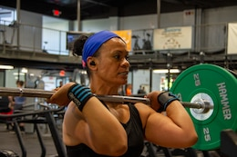 Sgt 1st Class Leilani Caracciolo, network manager noncommissioned officer in charge 1st Theater Sustainment Command (TSC), lifts a loaded barbell to an overhead position during her training for the 1,000-Pound Club at Otto Fitness Center at Fort Knox, Ky., July 17, 2019.