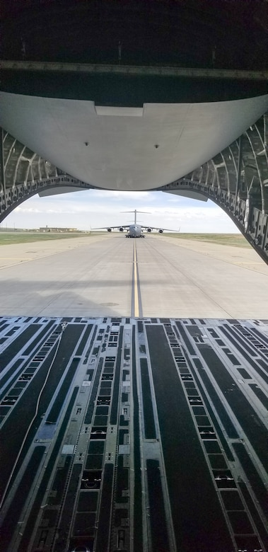 Maj. Dennis Martin, 225th Air Defense Squadron air battle manager, watches from the back of the C-17 he is flying in during Exercise Rainier War as four C-17s simulate dropping off cargo at Mountain Home Air Force Base, Idaho, June 26, 2019.  Martin is one of four air battle managers flying onboard the C-17s during the exercise in order to accomplish a portion of his training requirements to convert to a rated air battle manager.  (Courtesy Photo by Maj. Dennis Martin)