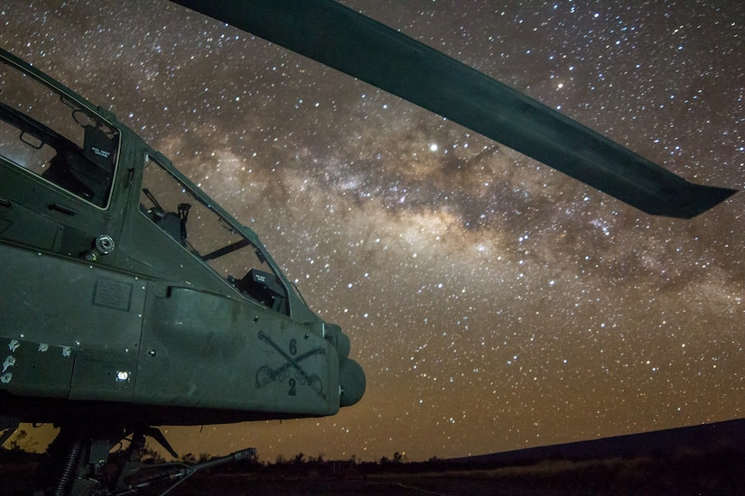 Army AH-64 Apache attack helicopter assigned to 2-6 Cavalry Regiment, 25th Combat Aviation Brigade, sits on flightline under night sky on FARP 17,