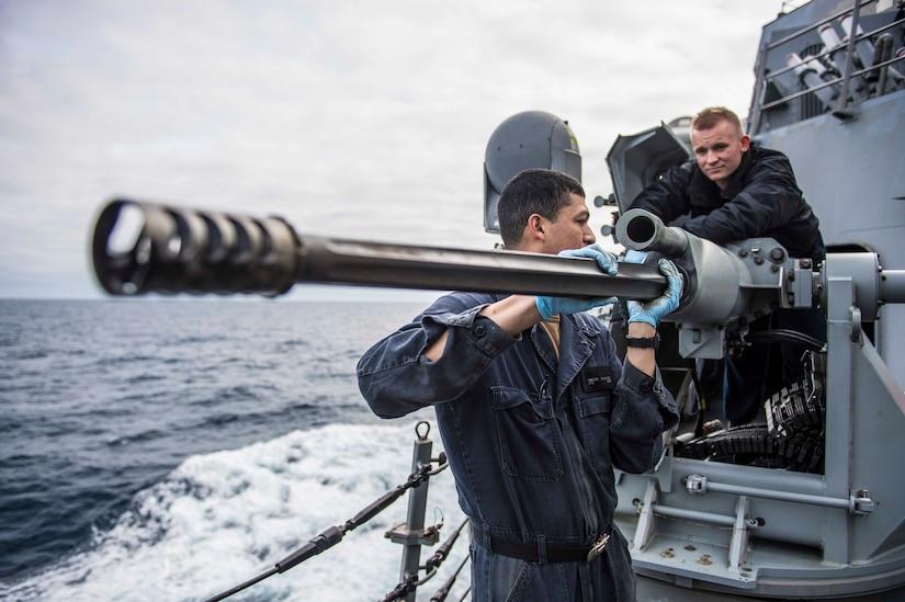 Fire controlman (left) and gunner's mate maintain Mark 38 25mm machine gun aboard USS Porter in Atlantic Ocean, March 5, 2019 (U.S. Navy/James R. Turner)