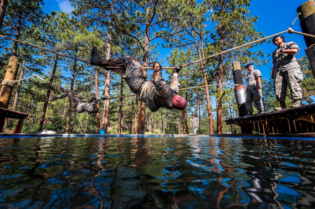 An airman crosses a rope that is over water while other airmen watch.
