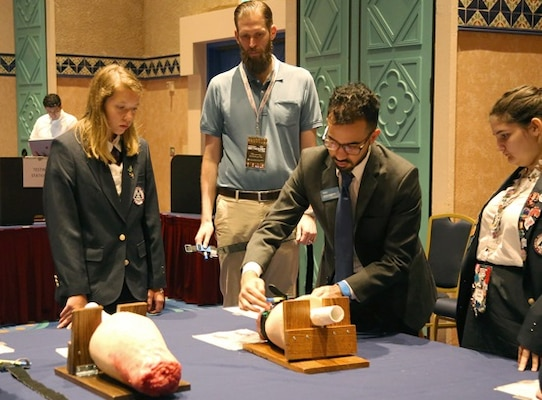 Uniformed Services University's Dr. Craig Goolsby (center) observes as high school students at a conference in Orlando, Florida, practice using a tourniquet after watching a web-based tutorial. Goolsby is researching effective teaching methods as part of a grant to develop a trauma first-aid course for students that incorporates elements of Stop the Bleed.