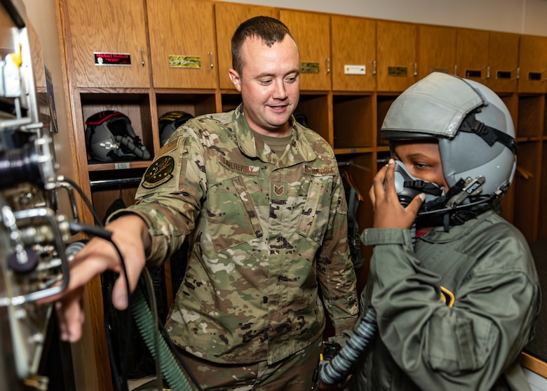 "Tech. Sgt. Christopher Lineberry, quality assurance, 509th Operations Support Squadron, turns on an oxygen tester to test an oxygen mask on Emil ""Batman"" Conley, from Lee Summit, Missouri, during a Pilot for a Day tour on July 19, 2019, at Whiteman Air Force Base, Missouri. Emil received a flight suit along with a patch with his call sign ""Batman"" the day prior at a pool party hosted by the 393rd Bomb Squadron. Emil has medulloblastoma, which is the most common malignant brain tumor for children, and accounts for about 20 percent of all childhood brain tumors. Whiteman AFB collaborates with St. Jude Children's Research Hospital to coordinate these tours. (U.S. Air Force photo by Senior Airman Thomas Barley)"