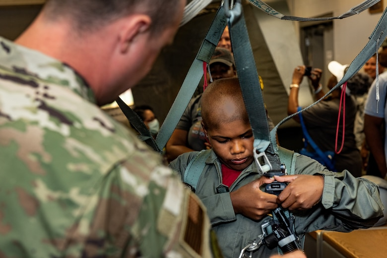 "Tech. Sgt. Christopher Lineberry, quality assurance, 509th Operations Support Squadron, assists Emil ""Batman"" Conley from Lee Summit, Missouri, with putting on an egress system harness during the Pilot for a Day tour on July 19, 2019, at Whiteman Air Force Base, Missouri. Aircrew flight equipment specialists perform maintenance and coordination of seats, hatches, canopies and modules, to ensure that pilots can make a safe escape in case of emergency. Emil has medulloblastoma, which is the most common malignant brain tumor for children, and accounts for about 20 percent of all childhood brain tumors. Whiteman AFB collaborates with St. Jude Children's Research Hospital to coordinate these tours. (U.S. Air Force photo by Senior Airman Thomas Barley)"
