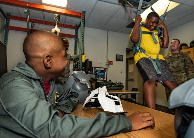 "Emil ""Batman"" Conley from Lee Summit, Missouri, laughs at his brother, Manny Conley, as he tests the egress system during his Pilot for a Day tour on July 19, 2019, at Whiteman Air Force Base, Missouri. Aircrew Flight Equipment specialist perform maintenance and coordination of seats, hatches, canopies and modules, to ensure that pilots can make a safe escape in case of emergency. Emil has medulloblastoma, which is the most common malignant brain tumor for children, and accounts for about 20 percent of all childhood brain tumors. Whiteman AFB collaborates with St. Jude Children's Research Hospital to coordinate these tours. (U.S. Air Force photo by Senior Airman Thomas Barley)"
