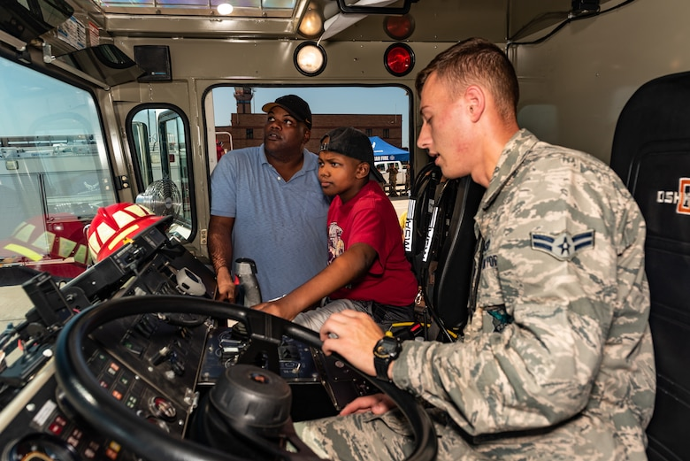 "Airman 1st Class Henry Schuermann, Firefighter, 509th Civil Engineer Squadron, teaches Emil ""Batman"" Conley and his father Marcus from Lee Summit, Missouri, how to shoot water out of a fire truck during the Pilot for a Day tour on July 19, 2019, at Whiteman Air Force Base, Missouri. Emil received a flight suit along with a patch with his call sign ""Batman"" the day prior at a pool party hosted by the 393rd Bomb Squadron. Emil has medulloblastoma, which is the most common malignant brain tumor for children, and accounts for about 20 percent of all childhood brain tumors. Whiteman AFB collaborates with St. Jude Children's Research Hospital to coordinate these tours. (U.S. Air Force photo by Senior Airman Thomas Barley)"