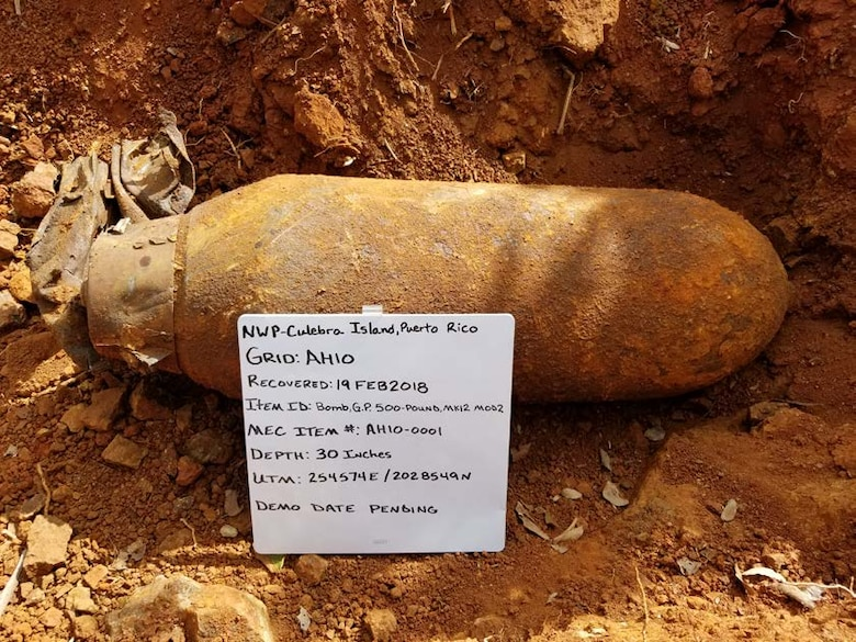 bomb with information written on a white board, NWP-Culebra Island, Puerto Rico; recovered 19FEB2018; Item ID: Bomb, G.P 500-Pound, MK12 MOD2; MEC ITEM#: AH10-0001; Depth: 30 Inches; UTM 254574E/2028549N; Demo Date Pending