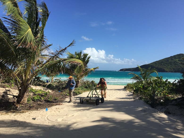 Two men are seen pushing Advanced Geophysical Classification equipment  on Flamenco Beach