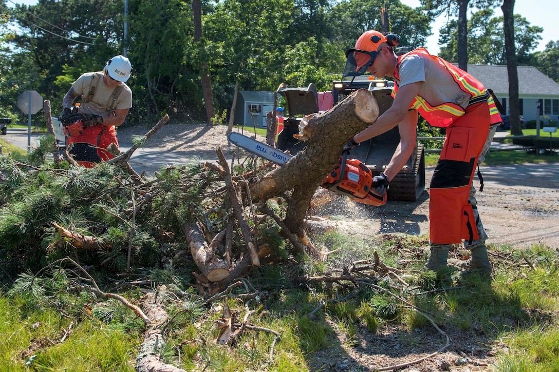 Two airmen saw through a downed tree on a residential street.