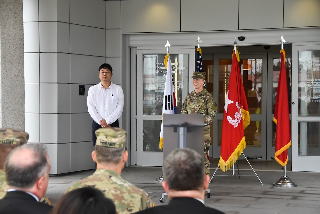 Brig. Thomas Tickner (center), U.S. Army Corps of Engineers (USACE), Pacific Ocean Division commander, and dignitaries gather in front of the new Brian D. Allgood Army Community Hospital, following the signing of the Acceptance Release Letter, Camp Humphreys, South Korea, July 24. (Photos by Antwaun J. Parrish)