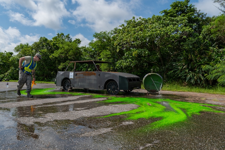U.S. Air Force Staff Sgt. Ryan Oke, fire emergency services training lead assigned to the 18th Civil Engineer Squadron, spreads green dye to simulate a hazardous chemical during a hazardous material training exercise July 11, 2019, on Kadena Air Base, Japan. The main objective of the HazMat training is for firefighters to familiarize themselves with hazardous materials and prevent them from spreading. (U.S. Air Force photo by Senior Airman Cynthia Belío)