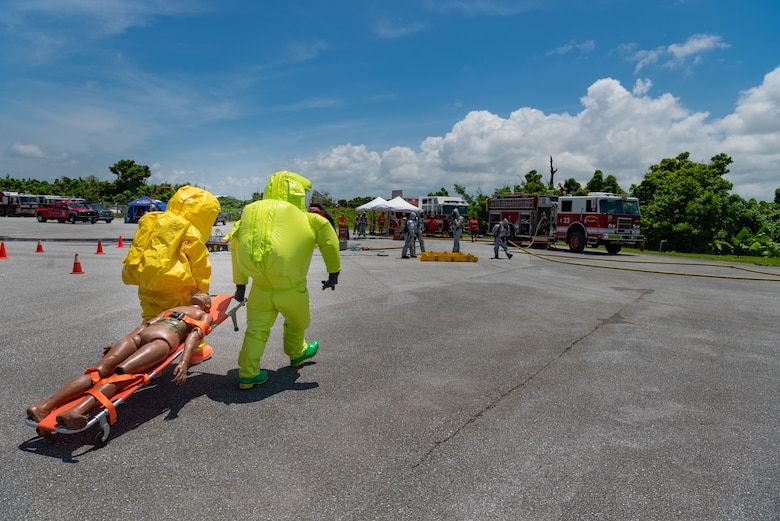 U.S. Air Force Airmen assigned to the 18th Civil Engineer Squadron carry a dummy toward a decontamination station during a hazardous material training exercise July 11, 2019, on Kadena Air Base, Japan. Airmen exposed to a hazardous chemical must be decontaminated before they take off their Level A suit to prevent further contamination. (U.S. Air Force photo by Senior Airman Cynthia Belío)