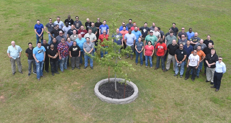 Members of the B-1B Integrated Battle Station program surrounding a Shumard Oak tree recently planted near the MROTC facility in recognition of IBS program completion. The group is comprised of modification members, work leaders and management who came together to efficiently modify the entire fleet of B-1 Lancer aircraft at Tinker Air Force Base. (U.S. Air Force photo/Greg L. Davis)